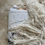 Image by Carolyn Hall: The Field guide on an off-white carpet under off-white tassels